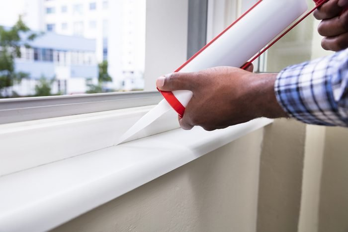 Close-up Of Person Hand Applying Silicone Sealant With Silicone Gun On Window
