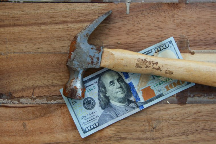Money and worker concept. hundred dollar on the wooden table with hammer
