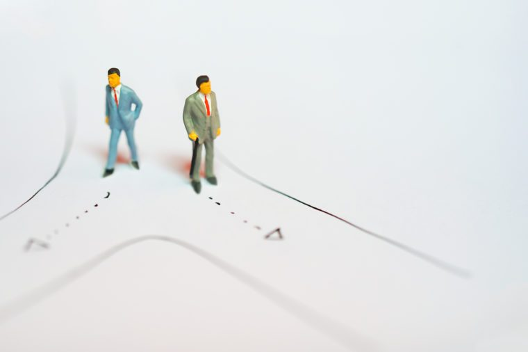 Miniature figures of Two business man standing on road selecting way to walk as decision making on white notebook paper drawing line with copyspace - business success backgroun concept
