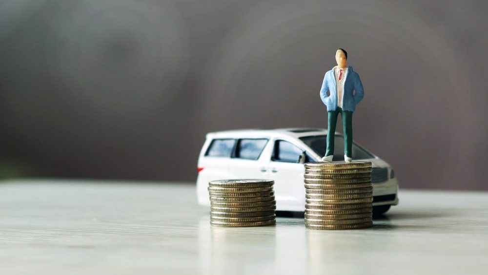 miniature people. The man standing on top of the coins and the car behind them.