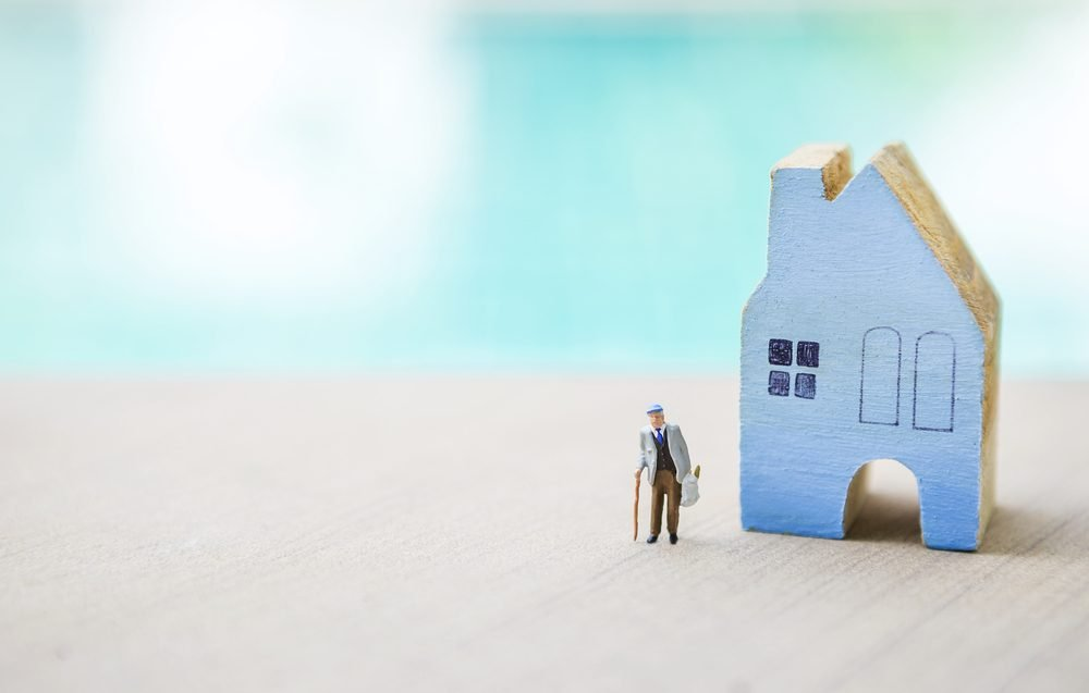 Miniature old man carry grocery bag with blue wooden miniature house over blurred blue background, outdoor day light