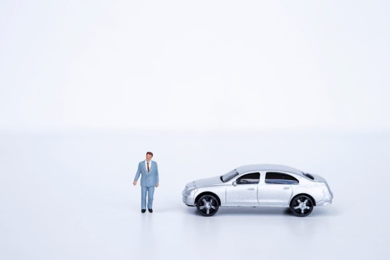 Miniature business man with model car on white background, business concept