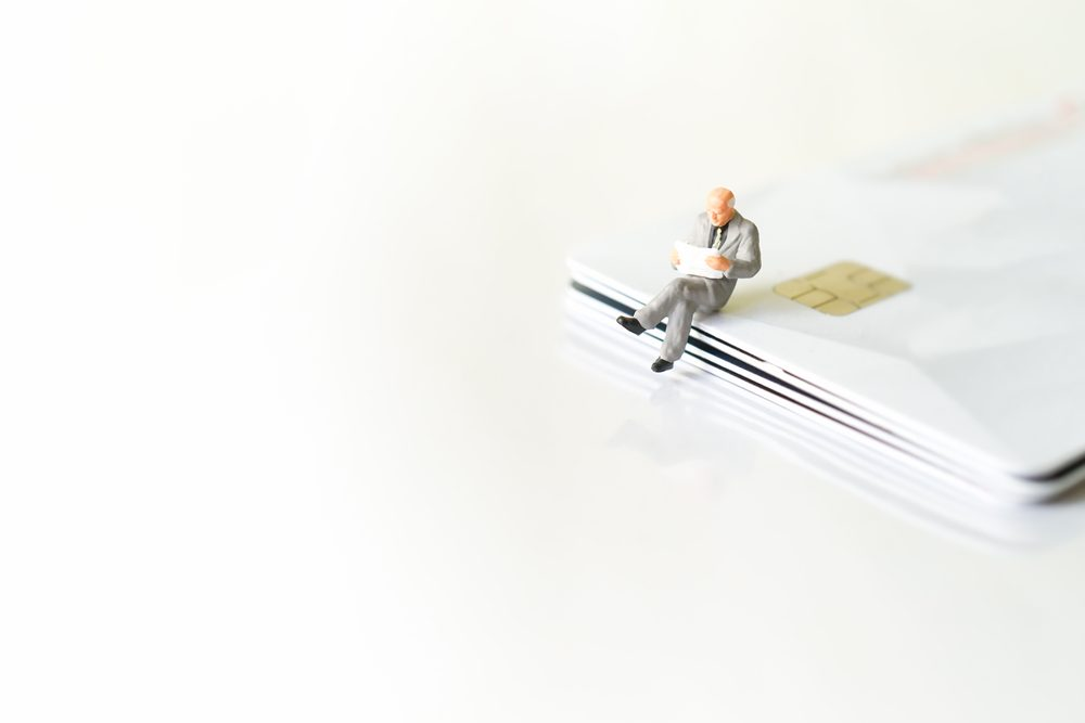 Miniature figure toy Business People sitting and reading newspaper on stack of credit cards, Banking Finance Technology, Shopping and e-commerce concept