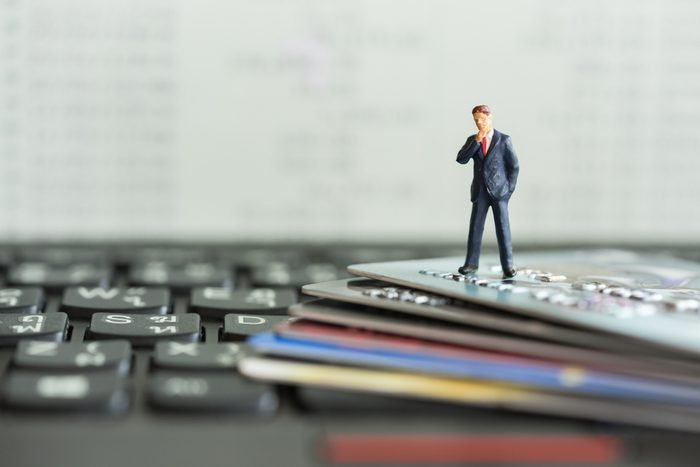 Shopping and e-commerce concept. Miniature people : Close up of miniature businessman on smart card and laptop keyboard.
