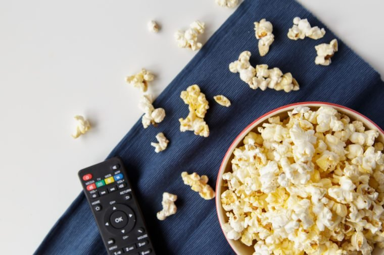 Popcorn with remote control on white table.