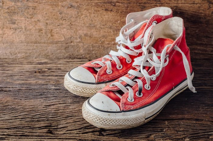 red sneakers on wooden floor with wooden background