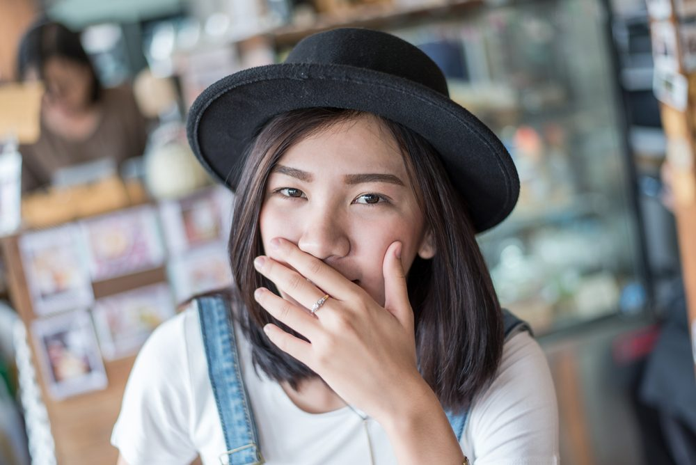 girl covers her mouth with her hands ,Asian shy girl with hat