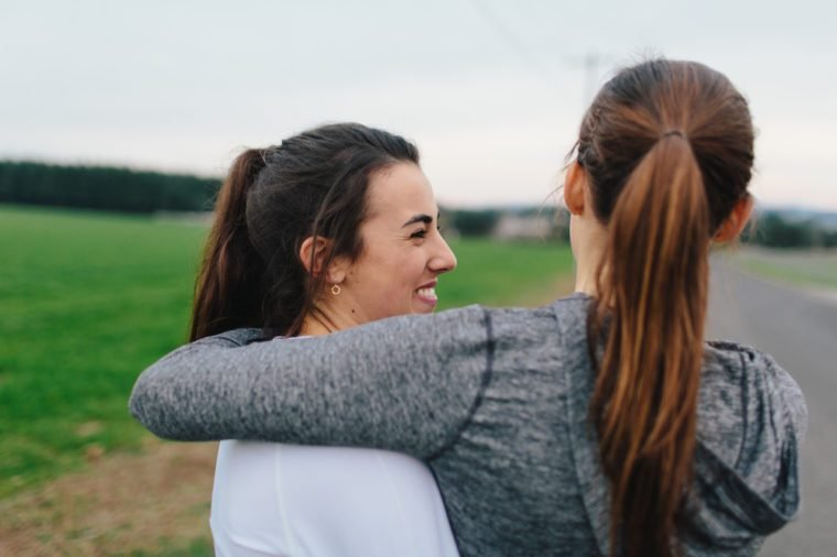 Two Beautiful Young Adult Women Arms around each other smiling