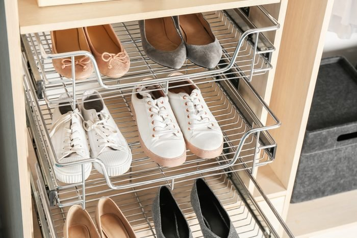 Different shoes on shelves of wardrobe closet