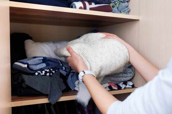 takes out clothing wool sweater with wardrobe