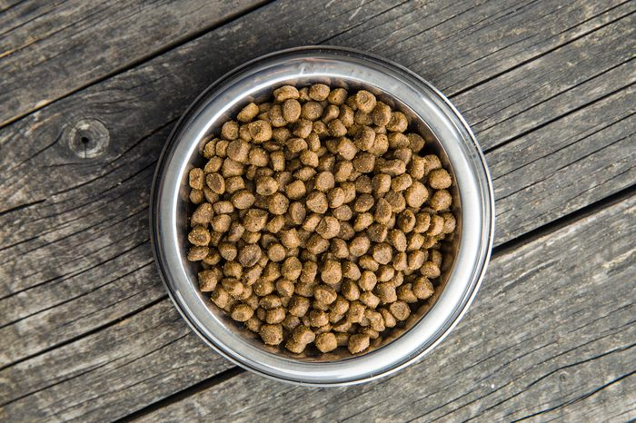 Dried food for dogs or cats in bowl on old wooden table. Top view.