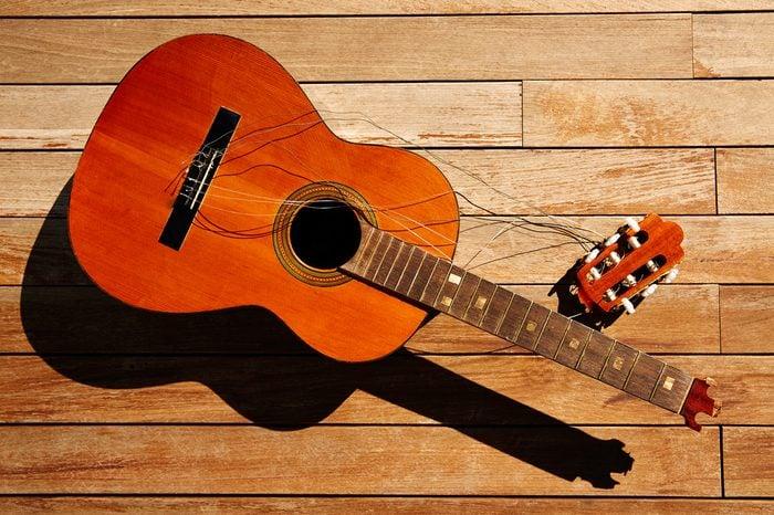 Broken spanish guitar neck on the wooden deck floor