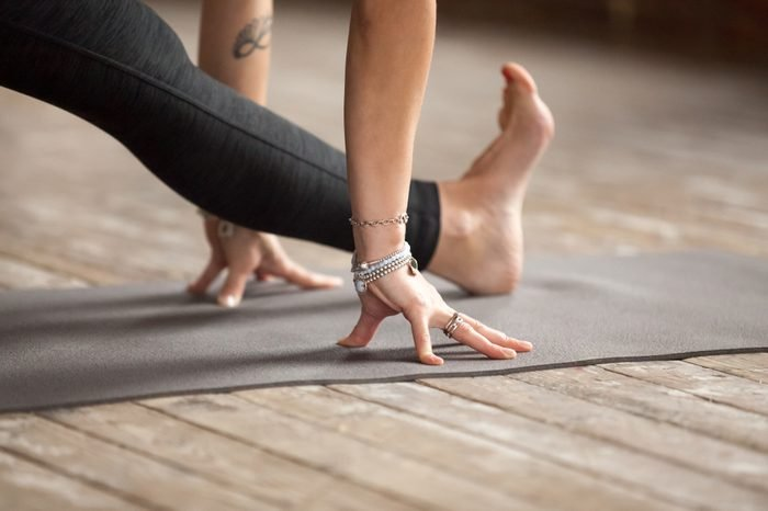 Young woman practicing yoga, doing Half splits exercise, Ardha Hanumanasana pose, working out, wearing sportswear, black pants, indoor close up, yoga studio. Healthy lifestyle concept