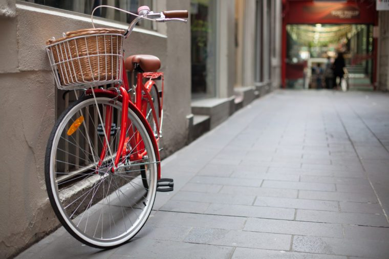 A shoppers red commuting bicycle with basket is parked in a lane-way in Melbourne, Australia, with shops in the background.