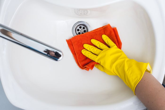 Woman's hand in yellow rubber glove wiping a sink. Cleaning concept.
