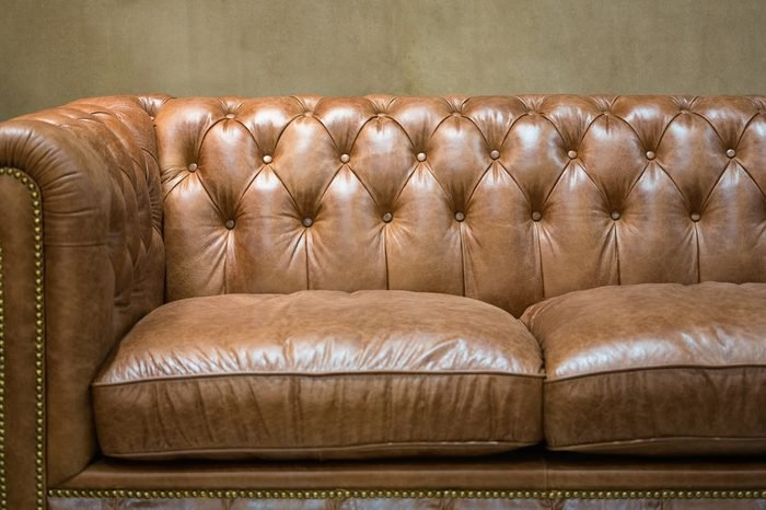 Vintage brown leather sofa with grunge gray wall living room.