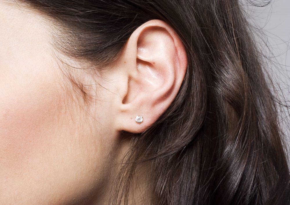 Young pretty woman ear closeup