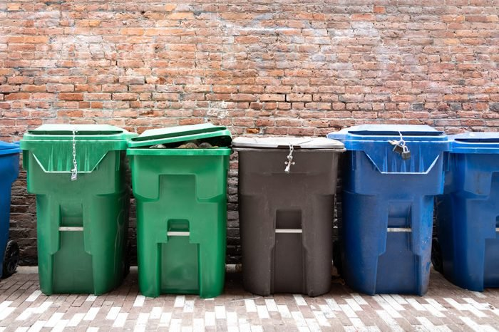 Row of green compost and clean green bins, beside blue recycling bins, with a brick wall background, and space for text on top