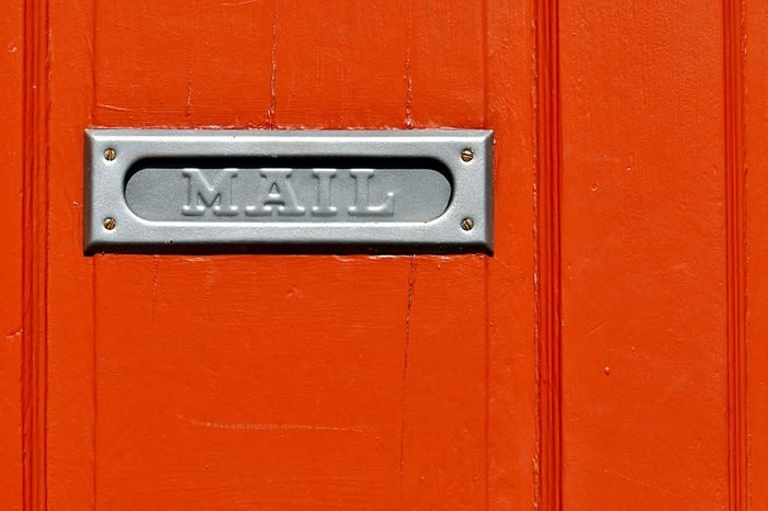 Closeup Of Metal Mail Slot On Orange Door In New Orleans French Quarter