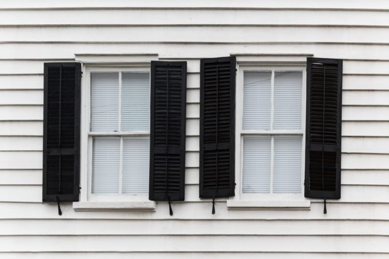 Two shut windows with open blinds on a wooden house