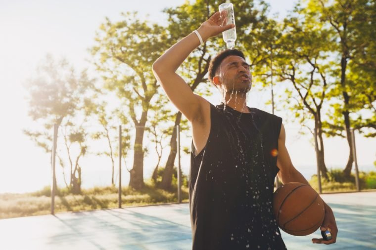 young black man spilling water on himself after training, basketball game, tired player, hot summer day