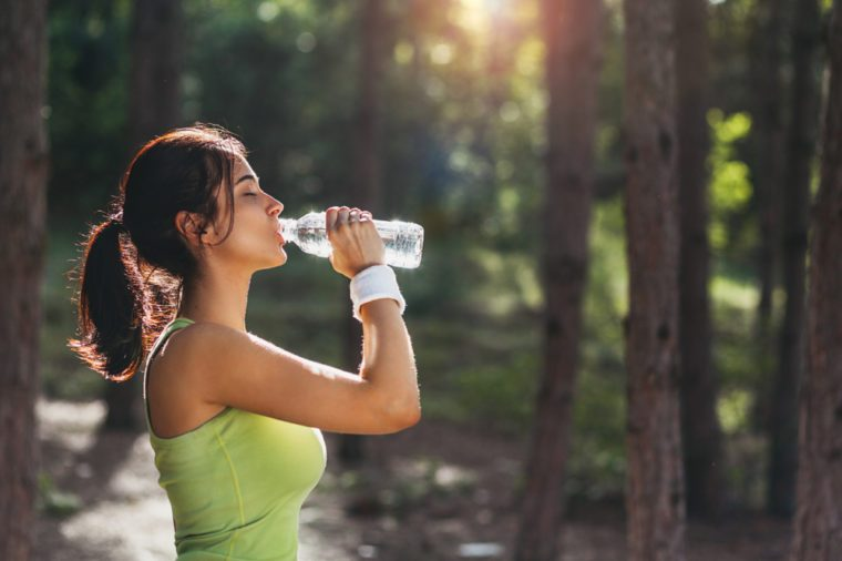 Girl drinking water from bottle in forrest