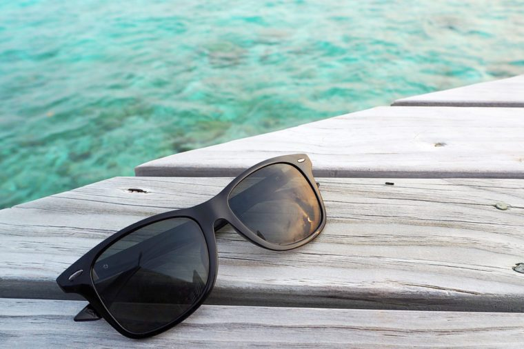 Sunglasses polarized lens on wooden deck over the sea