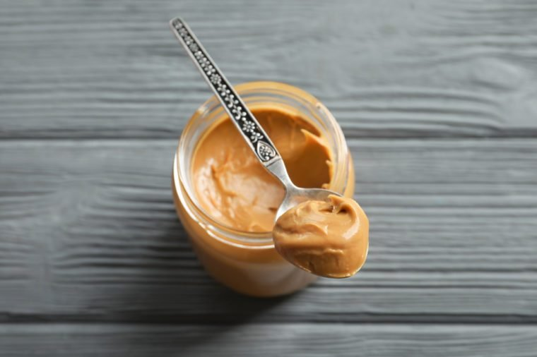 Spoon and glass jar with creamy peanut butter on wooden background