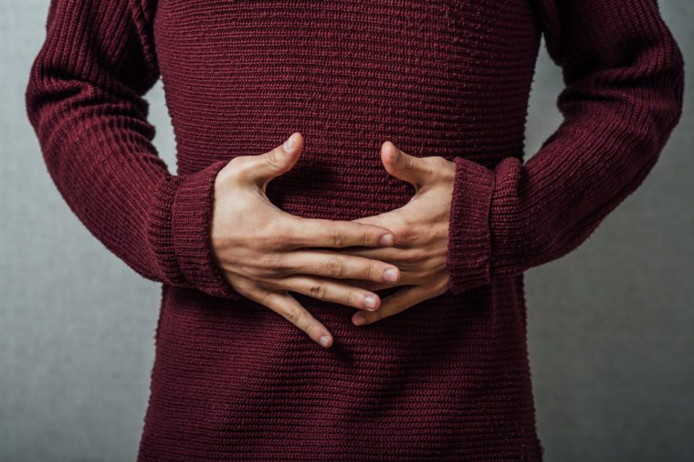 man holding his stomach in pain or indigestion