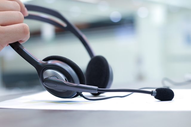 close up headset of call centre hotline at computer office room