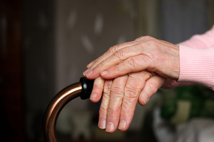 Elderly woman holds walking cane in her room. Senior lady experiencing bad service and conditions in retirement nursing home. Close up of mature woman's wrinkled hands laying on stick. Aging concept.