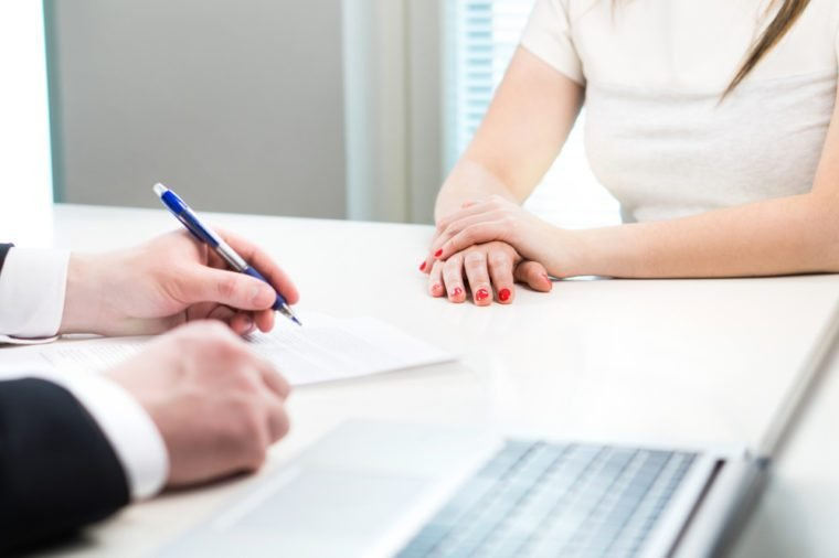 Young woman in job interview with business man. Interviewer writing notes. Lady having meeting with boss or executive manager.