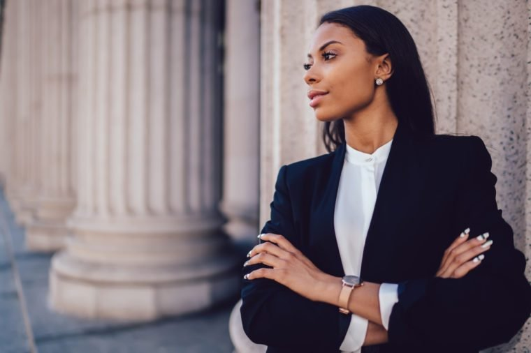 Female African American banker dressed in elegant black suit folding hands and looking on side standing against office building. Confident female entrepreneur with crossed arms looking on copy space