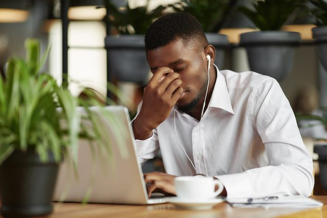 Bored, sad african man in white shirt, thinking, decided problem, working at cafe with laptop. Student male with closed eyes, holding head by hand. Freelancer have coffee break, listening music.
