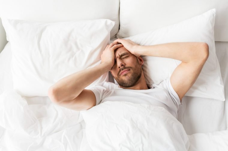 people, bedtime and rest concept - man lying in bed at home suffering from headache or hangover