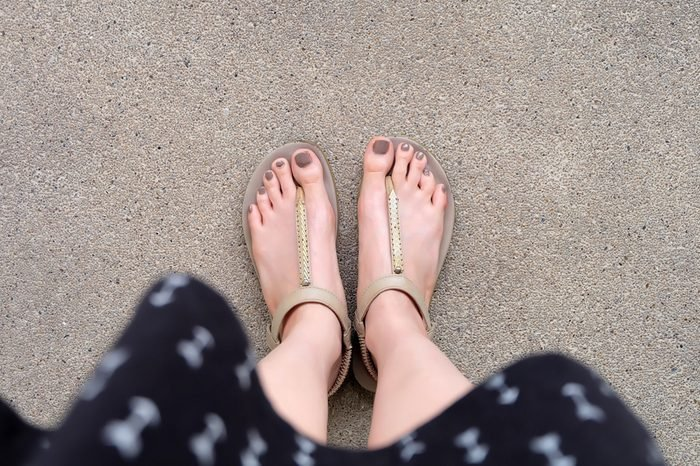Selfie Feet Wearing Gold Sandals and Dress on Ground Background Great For Any Use.