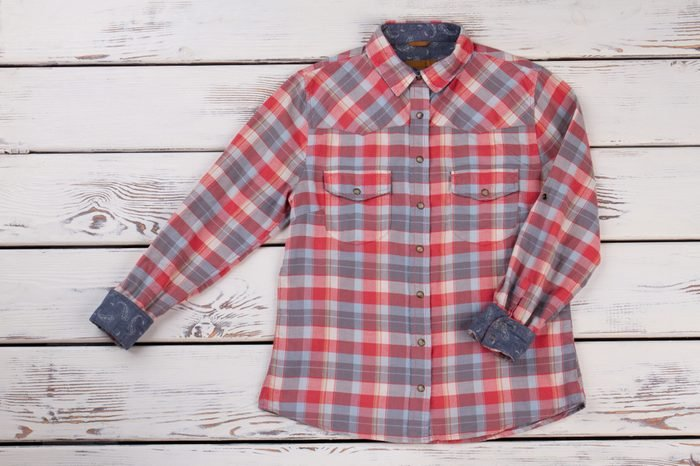 Stylish flannel plaid shirt on wooden shelf. Metal buttons and country pattern. Women's fashion trends.