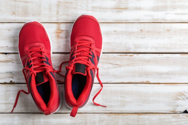 Red running shoe on white wood board