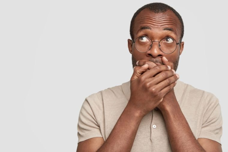 Photo of dark skinned young male tries to keep silence, covers mouth and looks upwards with embarrassed expression, isolated over white background, blank copy space for your promotional text