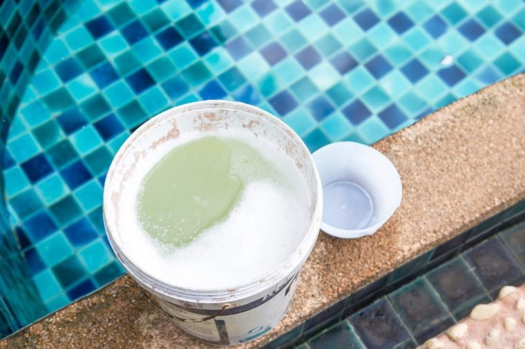 Chemical in plastic container on swimming pool edge, Water treatment for swimming pool, water disinfection with chlorine