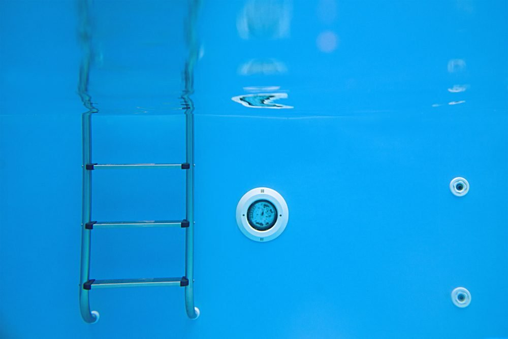 Background of view of the swimming pool with metal ladder underwater