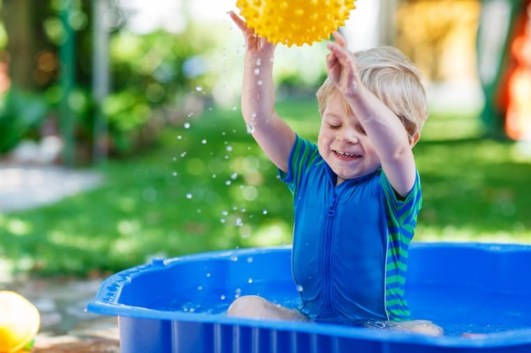 Little toddler boy having fun with splashing water and playing ball in summer garden pool