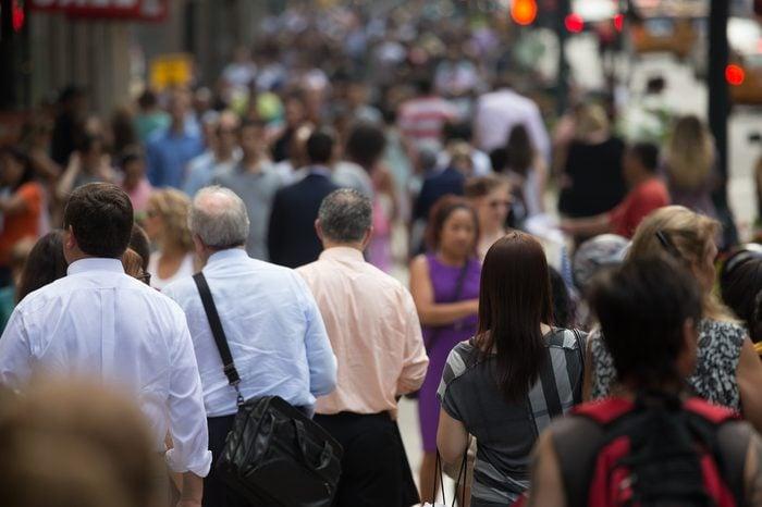 Crowd of people walking on street sidewalk in New York City