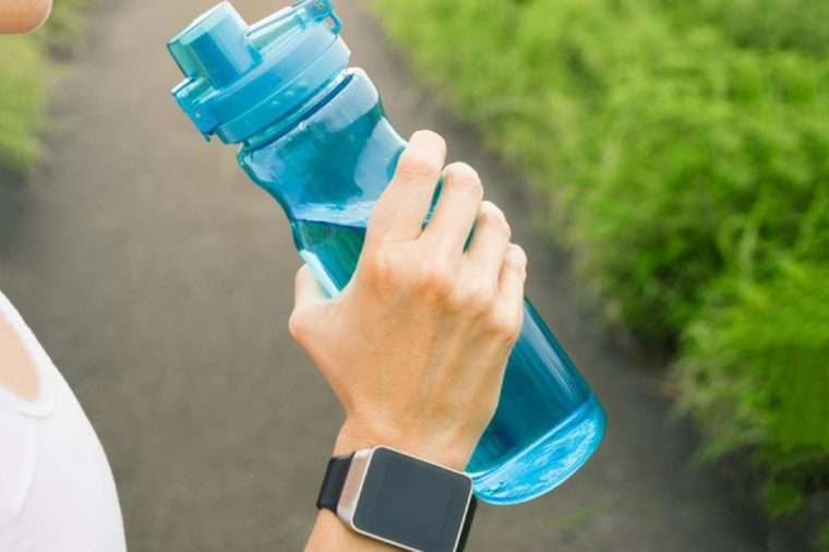 Female runner drinking bottle of water. Health and fitness concept.