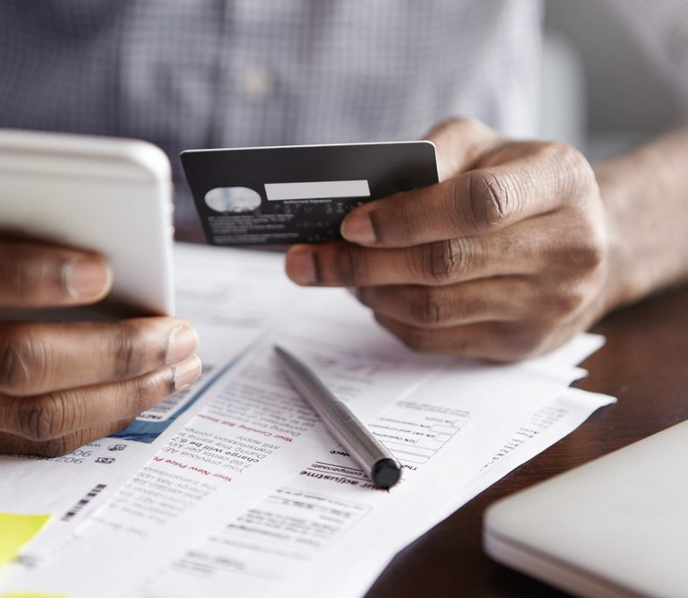 Online payment and shopping concept. Cropped shot of African-American male holding cell phone in one hand and credit card in other, making transaction, suing mobile banking app during lunch at cafe