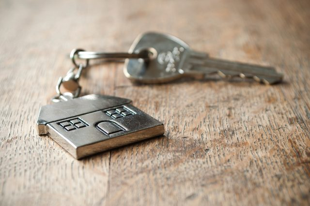 metallic key with house shaped key chain on wooden background