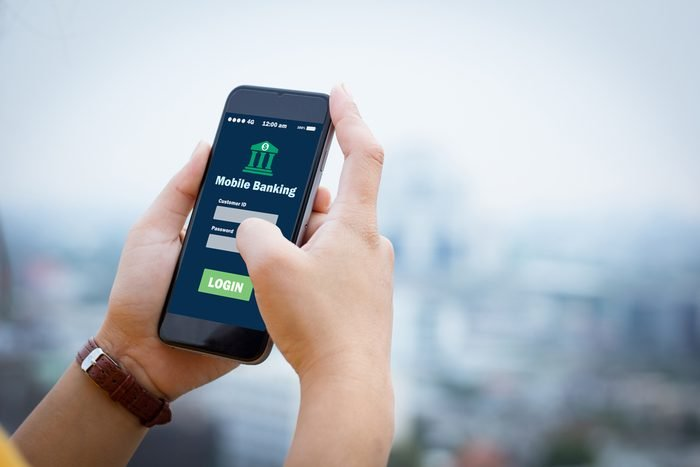 Female hands hold mobile banking on smart phone on blurred urban city as background