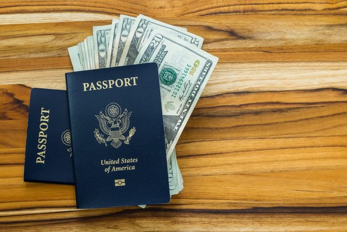 close up of two american passports and cash money on a wooden table for a travel concept