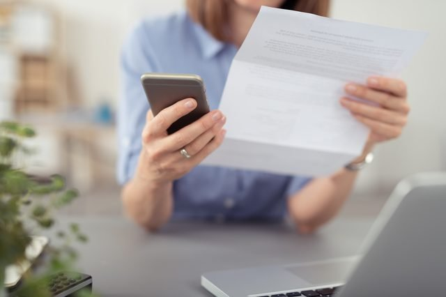 Businesswoman making a call on her mobile concerning a paper document she is holding in her hand, close up view