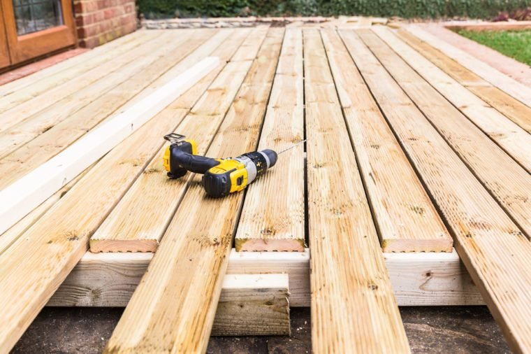 A new wooden, timber deck being constructed. it is partially completed. a drill can be seen on the decking.